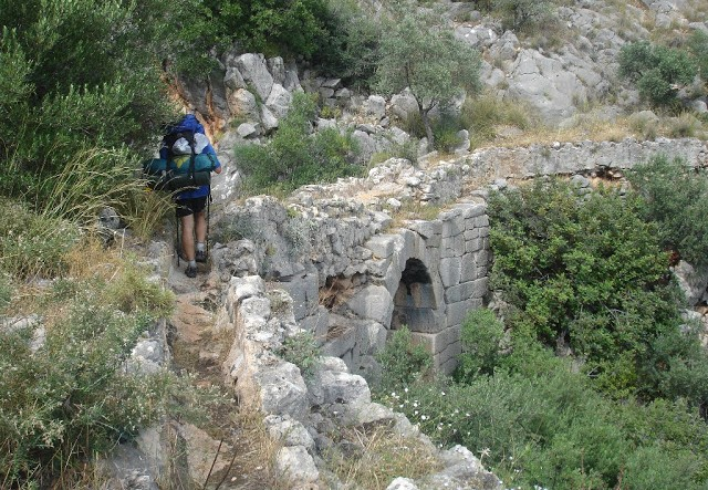 Hiker crossing the Roman bridge between Çavdır and Üzümlü